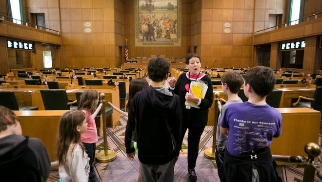 Volunteer Helene Searcy tells visitors about the legislative process as she shows them the House of Representatives during a tour of the Capitol on Monday, March 21, 2016. During spring break, tours of the building and the tower are running four times a day and are offered as part of the Spring Break Passport to Fun campaign, where participants can collect stamps at five downtown locations and enter a drawing for a basket of prizes.