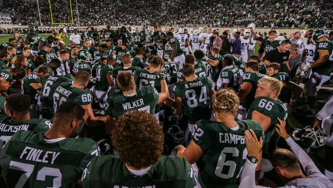 Michigan State Spartans players pray after the opening win against Furman at Spartan Stadium in East Lansing, Michigan, on Friday, September 2, 2016.