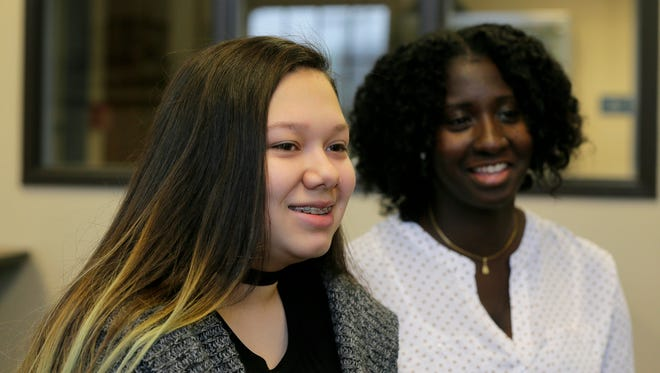 "(right) Kescy Mathurin, a mentor with the ""Give Something Back Foundation,"" which is sending six Long Branch High School students to college for free after they complete a mentoring program, and (left) Nina Gomez, 15, a sophomore at Long Branch High School, who is a scholarship student, talk about the program at the Long Branch Free Public Library in Long Branch, NJ Tuesday January 10, 2017."