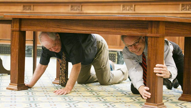 Senate President Peter Courtney (left) and former Oregon Supreme Court Chief Justice Thomas Balmer (right) under a table in the Oregon Supreme Court building as they participate in the Great Oregon ShakeOut earthquake drill on Oct. 20, 2016.