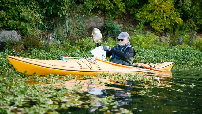 Pat Carey picks up a plastic bottle from the Willamette Slough as he volunteers for the Great Willamette River Clean Up on Saturday, Oct. 7, 2017. The clean up, organized by Willamette Riverkeeper, takes place at sites all along the Willamette River. Several took to the water in kayaks and paddle boards to pick up trash from the riverbanks around Minto Brown Island Park and the slough.