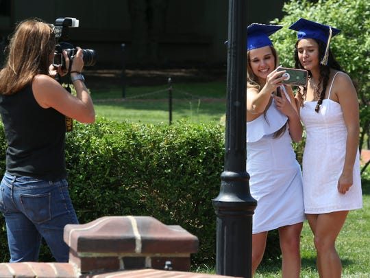 University of Delaware seniors Emma Charlton of Berwyn, Pa., and Alina Libowitz of Longmeadow, Mass. (right)  take part in a bucket list experience - photos and wading in the fountain on the Green as  Emma's mother, Lynn photographs them Wednesday.