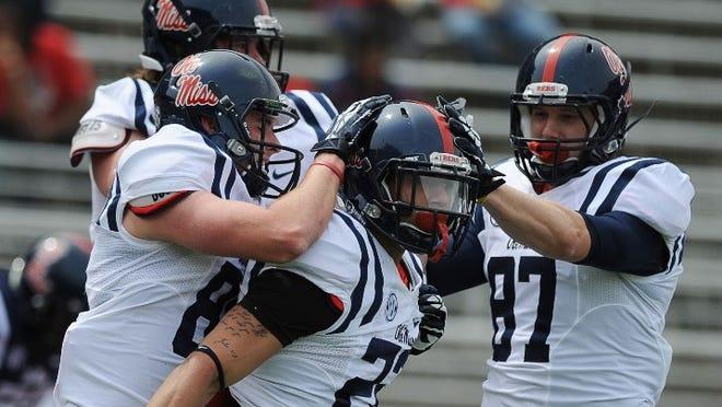 Teammates congratulate Jordan Wilkins, center, following a score during Saturday's Grove Bowl in Oxford.