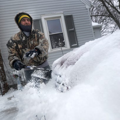 John Busse clears snow from a car during a spring snow