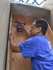 Roger Reyes secures wooden shutter to the wall of Infusion in Tamuning on July 3, in preparation for Tropical Storm Chan-hom.