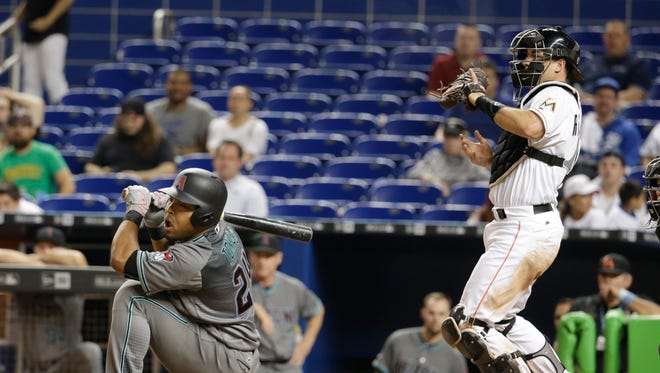 Arizona Diamondbacks' Yasmany Tomas, left, moves away from a close pitch as Miami Marlins catcher J.T. Realmuto looks on during a baseball game, Tuesday, May 3, 2016, in Miami. The Marlins defeated the Diamondbacks 7-4.