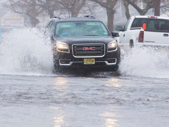 Cars struggle to drive along Broadway in Point Pleasant Beach as local streets flood with the tide and heavy rains.