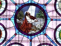 CALVARY (EPISCOPAL) CATHEDRAL: This stained glass window at the west end, depicting John the Baptist breaking a path in the wilderness, commemorates Bishop William Hare, who was a pioneer missionary for the church and founded the Sioux Falls church. The cathedral at Ninth and Main was built in 1889 and includes a variety of stained glass windows throughout. The paintings encircling this window show how the Episcopal Church came to South Dakota. The window was designed in 1911 and shipped from New York. In 1946, it was discovered that the inner face of the window had been covered by thick varicolored glass, which prevented the true color and detail from being revealed until it was removed.