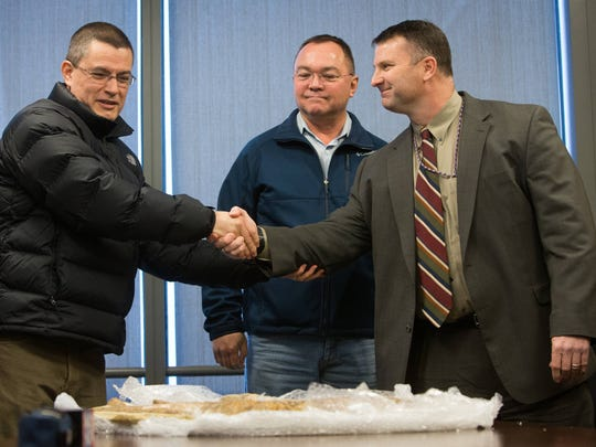 FBI Special Agent John Webb, right, shakes hands with Brazil Federal Police Commissioner Mauricio Valeixo as Brazilian Assistant Attaché Marcos Koren looks on during a brief ceremony Monday, transferring custody of three fish fossils for return to Brazil, where they were stolen.