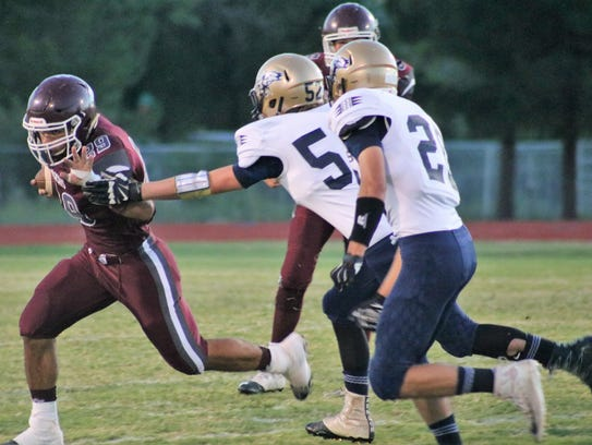 Tularosa's Caleb Ball, left, tries to run past a Ruidoso