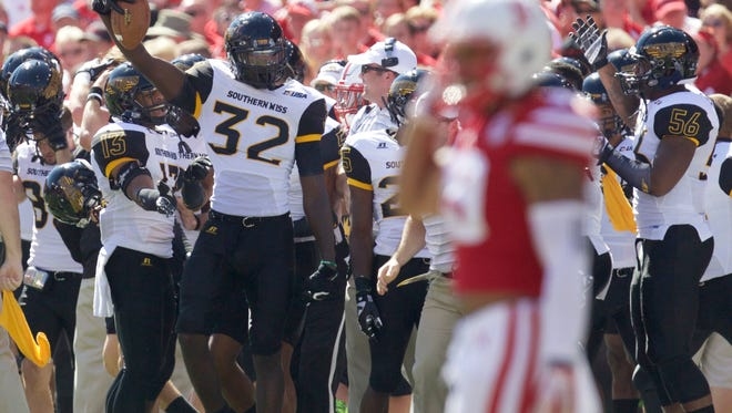 Southern Mississippi  defensive lineman Xavier Thigpen (32) holds up the ball after recovering an onside kick against Nebraska on Saturday.