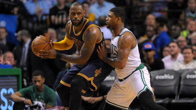 Cleveland Cavaliers forward LeBron James controls the ball while being guarded by Boston Celtics guard Marcus Smart during the first half in game one of the Eastern conference finals of the NBA Playoffs at TD Garden.