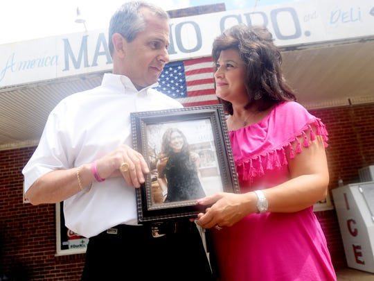 Venson Maggio and Sharon Peters Maggio hold a photo of their daughter Melissa, who was killed in a car accident. They donated land to the Fuller Center to build a house in her honor for a veteran.