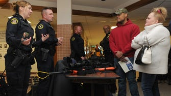 Milwaukee K-9 Handler, Christina Marshall, left, and Police Officer Tactical Enforcement Unit Matthew Seitz talk with Izayah Potis, 23 and his mother Dawn Potis during the Milwaukee Police Department open house and information session on March 25, 2017.
