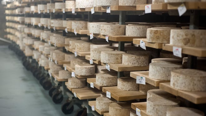 Rounds of cheese age on wooden boards in a cellar at Jasper Hill Farm in Greensboro earlier this year.