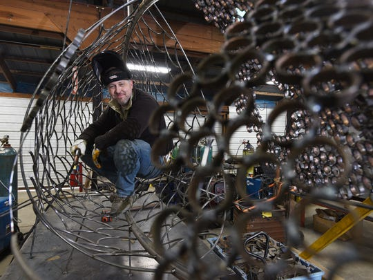 David Griesmyer pauses while welding one of the fish sculptures to be installed along Ohio 60 as part of the Corridor of Art project.