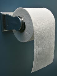 A full roll of toilet paper in a stall.