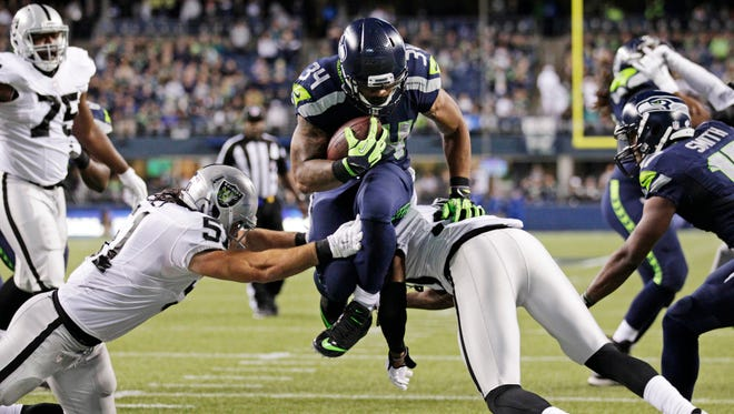 Seattle Seahawks running back Thomas Rawls leaps above Oakland Raiders Ben Heeney, left, and SaQwan Edwards, right, to score a touchdown on a run in the second half of a preseason NFL football game, Thursday, Sept. 3, 2015, in Seattle.