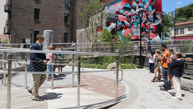 Visitors at the walkway and seating area at the new Mill Street courtyard and daylighting of the Saw Mill River in Yonkers. In the background is a mural, recently created, by Dutch artist Eelco van den Berg.