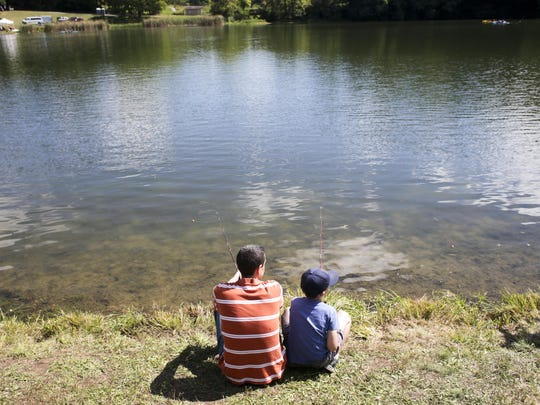 Doug Sapp (left), Indianapolis, sits with his son Brendan, 8, who's taking his second try at fishing during The Hoosier Outdoor Experience, in 2013.