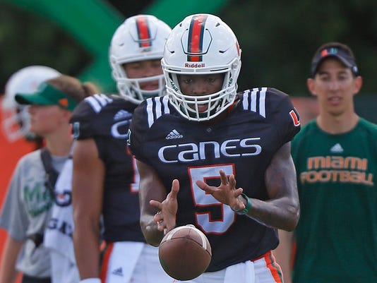 FILE - In this Aug. 14, 2017, file photo, Miami freshman quarterback N'Kosi Perry runs a drill during the NCAA college football team's Media Day in Coral Gables, Fla. Perry, who is 6-4, is the nation's No. 7 dual-threat quarterback prospect in his class according to the 247Sports Composite. (Carl Juste/Miami Herald via AP, File)