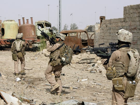 U.S. Marines aim their weapons as they walk through the rubble of an industrial building in the southern part of Fallujah, Iraq, in this 2007 file photo.