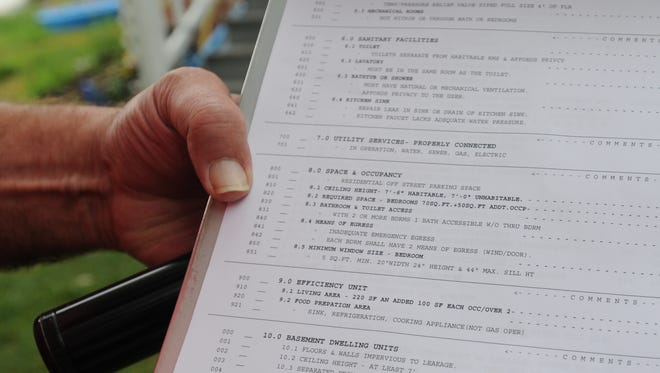 A Port Huron rental inspector examines his checklist before entering a three-unit apartment building on Griswold Street