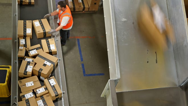 Workers box up packages to send out at the Amazon Whitestown Fulfillment Center.