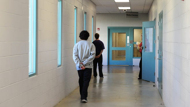 This file photo shows two boys walking along a hallway at Wittenberg Hall at the Jan Evans Juvenile Justice Center.
