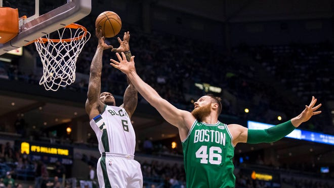 Bucks guard Eric Bledsoe skies to grab a pass for an alley-oop dunk against Celtics center Aron Baynes late in the season.