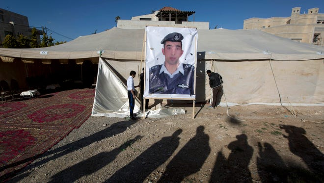 A banner with a picture of Jordanian pilot Lt. Muath al-Kaseasbeh is being raised by workers near a tent prepared for receiving supporters, in Amman, Jordan, on Jan. 30, 2015.