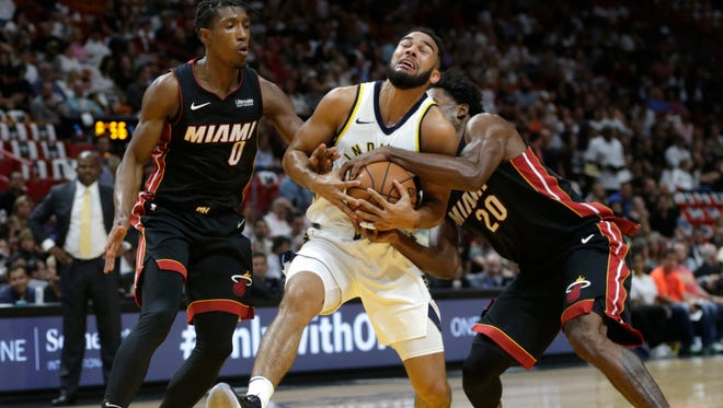 Indiana Pacers' Cory Joseph, center, drives to the basket as Miami Heat's Josh Richardson (0) and Justise Winslow (20) defend during the first half of an NBA basketball game, Saturday, Oct. 21, 2017, in Miami.