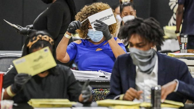 Election workers sort absentee ballots in Atlanta earlier this month.