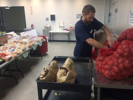 Volunteer worker Jim Arbogash fills grocery bags with