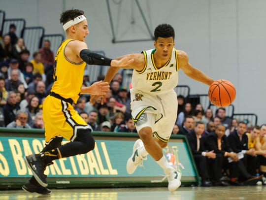 Vermont's Trae Bell-Haynes (2) dribbles the ball down the court past UMBC's K.J. Maura (11) during the men's basketball game between the UMBC Retrievers and the Vermont Catamounts at Patrick Gym in January.