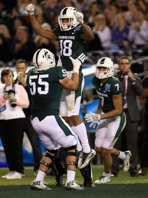 Jordan Reid #55 congratulates Felton Davis III #18 of the Michigan State Spartans after his pass play touchdown against the Washington State Cougars during the first half of the SDCCU Holiday Bowl at SDCCU Stadium on December 28, 2017 in San Diego, California.