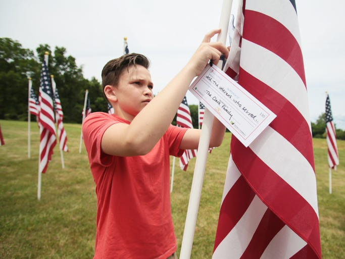 Jake Clark, 12, of Bedminster, hangs a tag on the flag