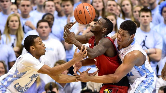 Jan 10, 2015; Chapel Hill, NC, USA; North Carolina Tar Heels guard Nate Britt (0) and forward Kennedy Meeks (3) fight for the ball with Louisville Cardinals guard Chris Jones (3) in the second half. The Tar Heels defeated the Cardinals 72-71 at Dean E. Smith Center. Mandatory Credit: Bob Donnan-USA TODAY Sports