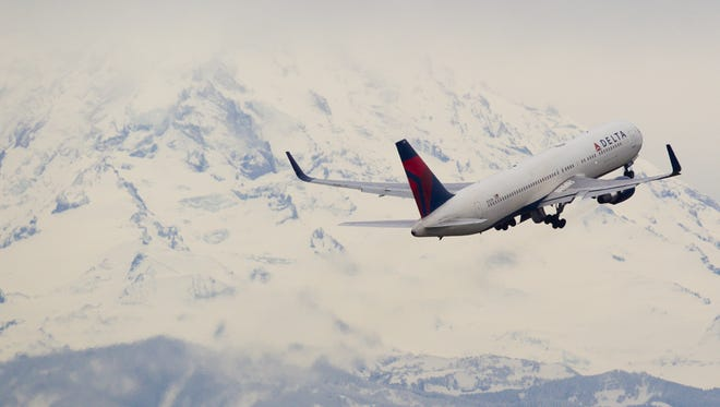 A Delta Air Lines Boeing 767-300 bound for Asia climbs out of the Seattle area and past a looming Mt. Rainier on December 26, 2015.