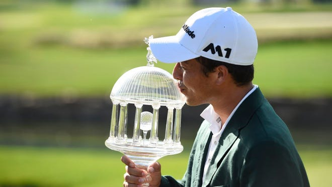Xander Schauffele kisses the championship trophy after winning The Greenbrier Classic at The Old White TPC.