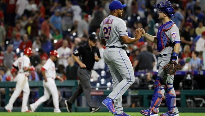 New York Mets catcher Devin Mesoraco, right, and relief pitcher Jeurys Familia celebrate after a baseball game against the Philadelphia Phillies, Friday, May 11, 2018, in Philadelphia. New York won 3-1.