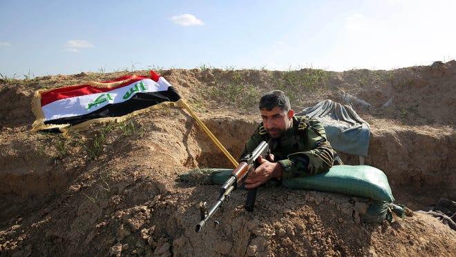 A Shiite militia fighter aims his weapon with the Iraqi flag in the background, on the frontline just outside the city of Kirkuk, Iraq on Feb. 15, 2015 photo.