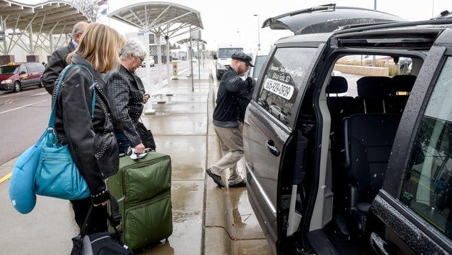 Travelers load their luggage into a taxi outside of Sioux Falls Regional Airport on Monday Nov. 6, 2017.