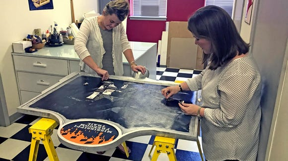 Megan Slaughter and Britt Carter of Hammons & Associates remove remnants from the vinyl graphic, which contained text and photographs that vandals scraped away from the historic Emmett Till marker. The next step will be to reapply photographs and text to the vinyl.