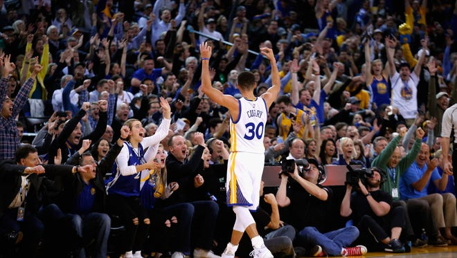 Stephen Curry of the Golden State Warriors helps fire up the crowd at Oracle Arena in Oakland. The Warriors have a 38-game winning streak at home.