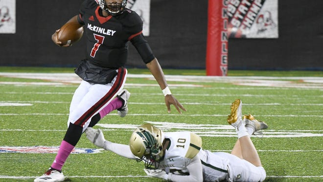 McKinley quarterback Elijah Wesley escapes diving GlenOak defender Luke Wiery, Oct. 18, 2019.