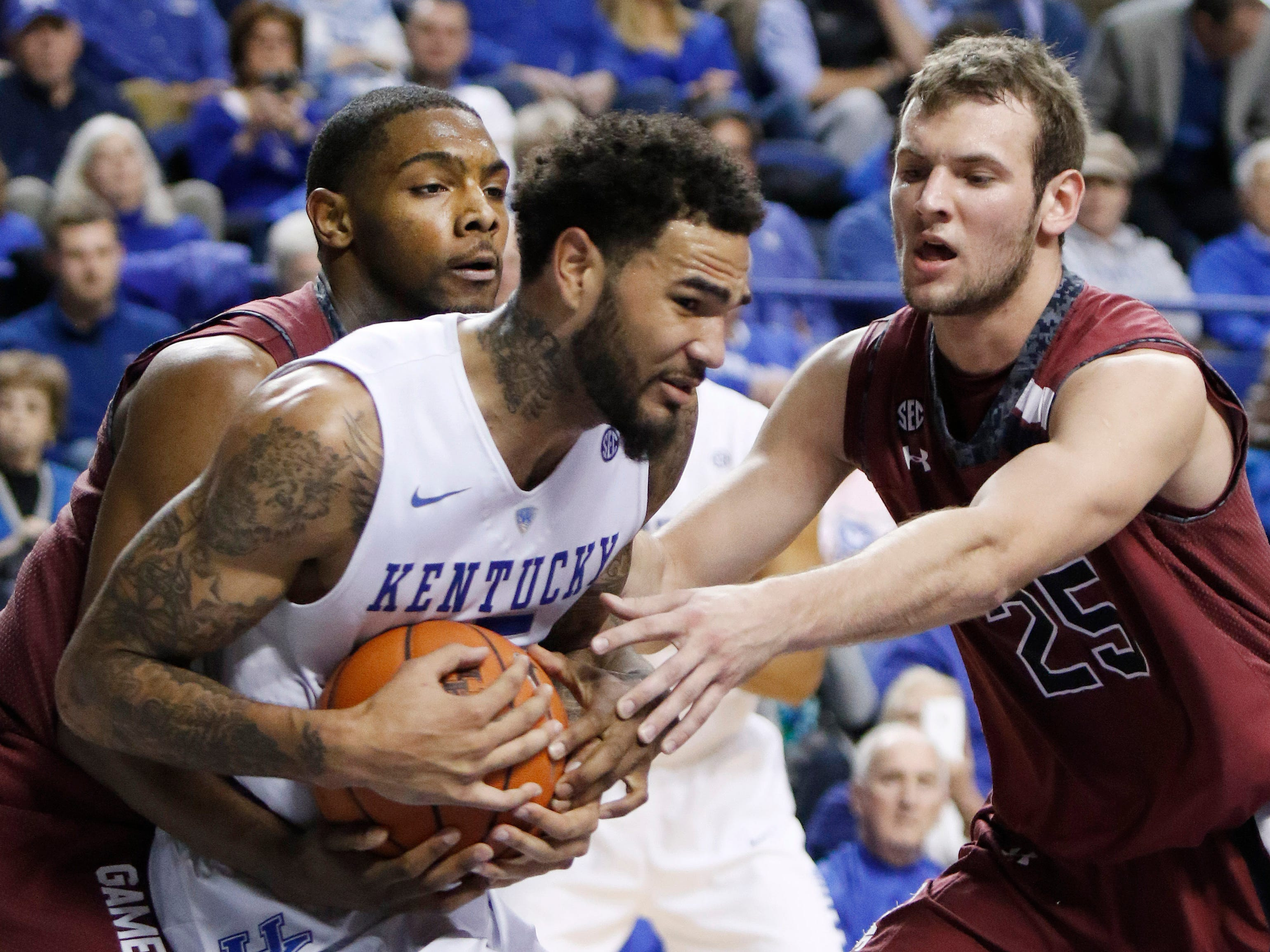 Kentucky's Willie Cauley-Stein, center, is pressured by South Carolina's Sindarius Thornwell, left, and Mindaugas Kacinas during the second half of an NCAA college basketball game, Saturday, Feb. 14, 2015, in Lexington, Ky. (AP Photo/James Crisp)