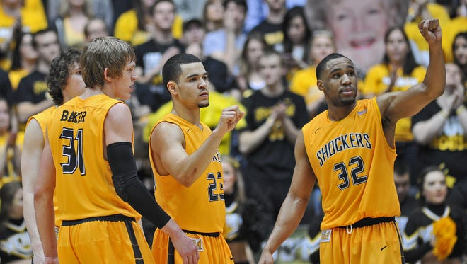 Fred VanVleet #23, Tekele Cotton #32 and Ron Baker #32 of the Wichita State Shockers look to the bench against the Southern Illinois Salukis during the second half on February 11, 2014 at Charles Koch Arena in Wichita, Kansas.  Wichita State won 78-67.