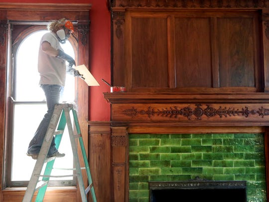 Heather Sullivan of Sullivan Restoration, refinishes the mahogany that will be the library and office.