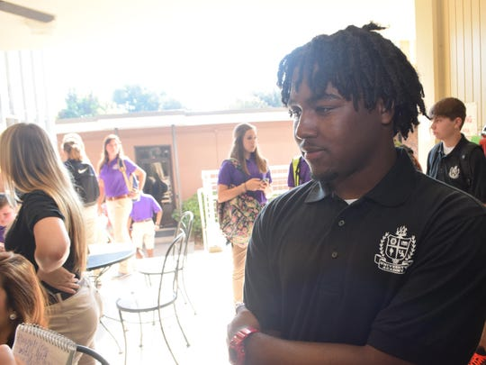 University Academy of Central Louisiana junior Davion Henton talks about the first day of school during a break Wednesday.